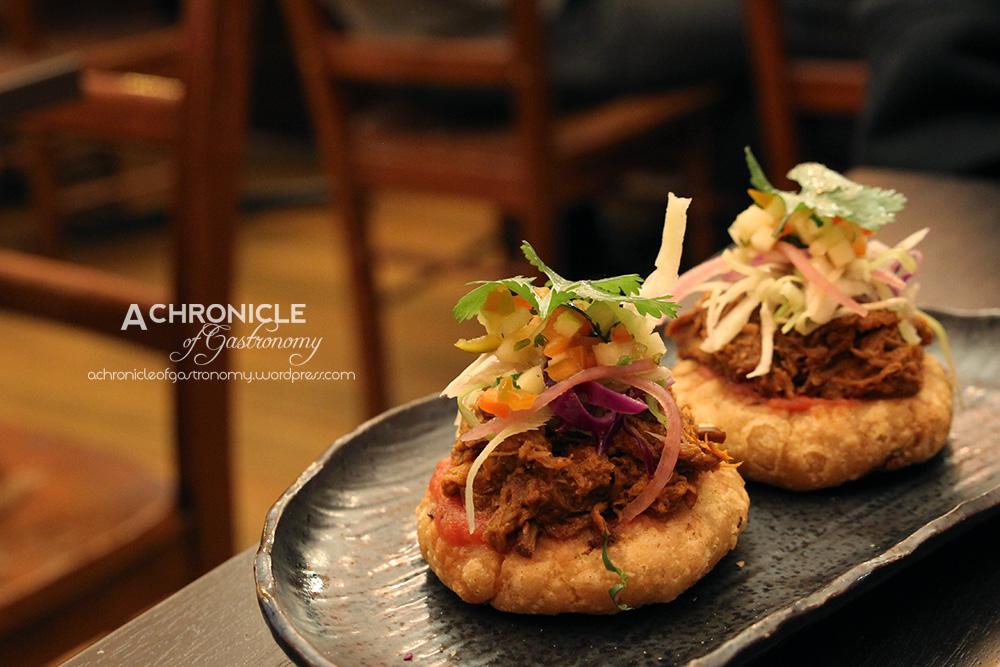 Pork Sopes - Thick White Corn Tortilla filled w. Refried Beans, topped w, Slow Cooked Pork, Pickled Onions, Pico de Gallo and Coriander