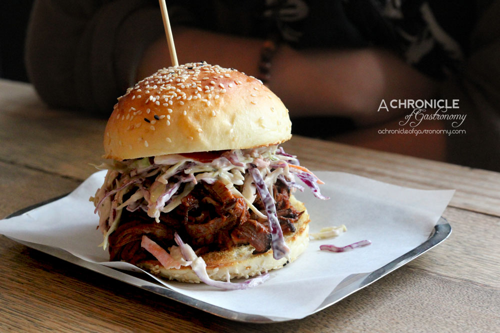 The B-East Red Eye Pulled Pork - 12hr Dry Rubbed Pulled Pork in Espresso and Dark Honey BBQ Sauce w. Smoked Jalapeno and Lime Slaw on Brioche Bun ($14)