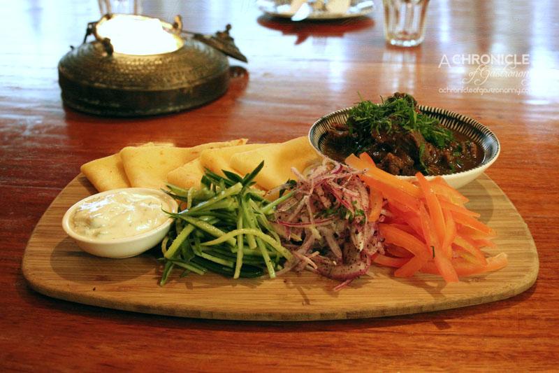 Koy - Raki Goat Roll Up - Raki Infused Goat Served w. Crepes, Sumac Onion, Fresh Tomato & Cucumber w. Herbed Yoghurt ($19.50)