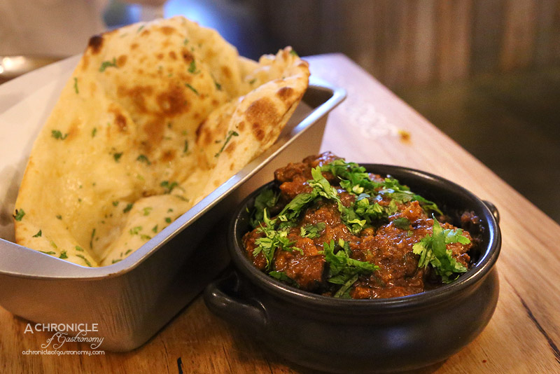 Mukka - Slow Cooked Goat Curry 4 hrs, Tomato and Onion Gravy, Coriander, Garlic Butter Naan ($20 + $3.50)