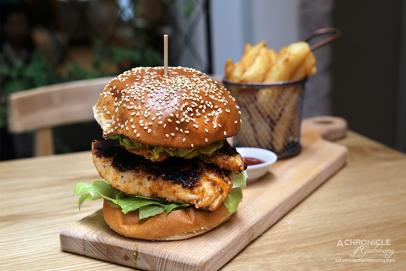 Cafe AMBA - Supreme Chicken Burger - Toasted brioche, marinated chicken breast strip, baby cos lettuce, tomato, smashed avocado & chipotle aioli served with chips & tomato sauce ($16)