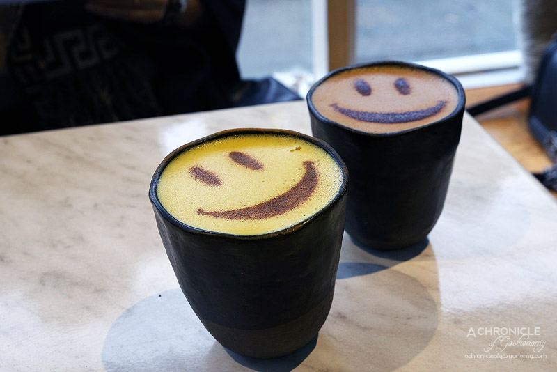 Serotonin Eatery - Golden Latte - Turmeric, ginger, cinnamon, black pepper, coconut milk ($8), Cacao coconut latte - 70% dark hot chocolate with raw cacao, grated cacao butter, coconut milk + espresso ($8)