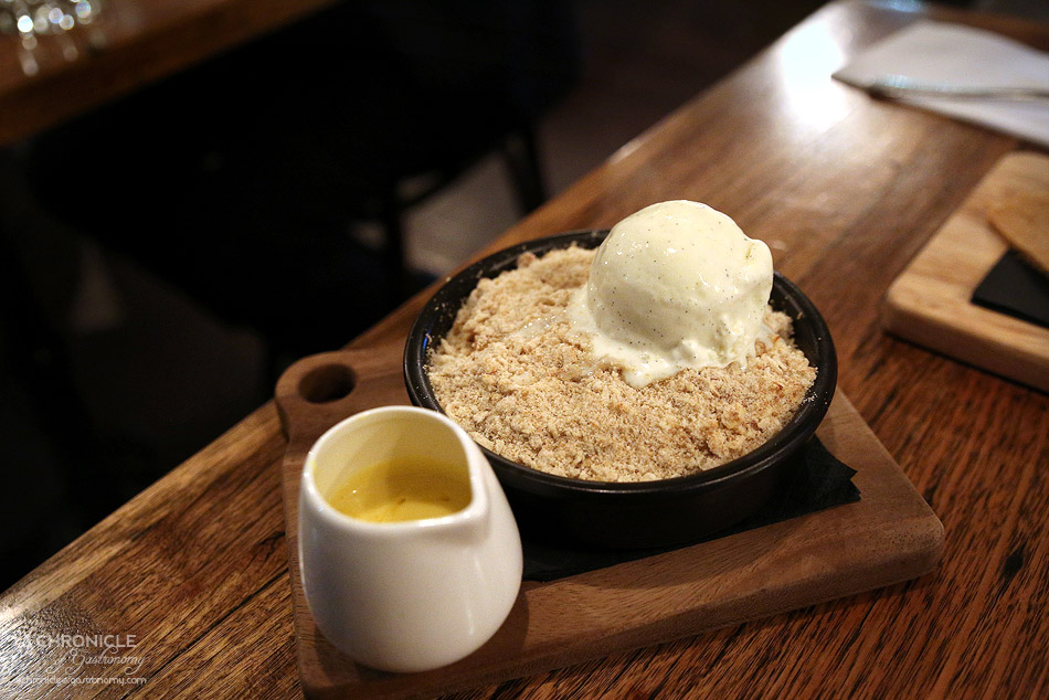 The Fifth Province - Peach crumble topped with biscuit and honey oat crumble, served with homemade custard and lemon cream, vanilla ice cream ($9.50)