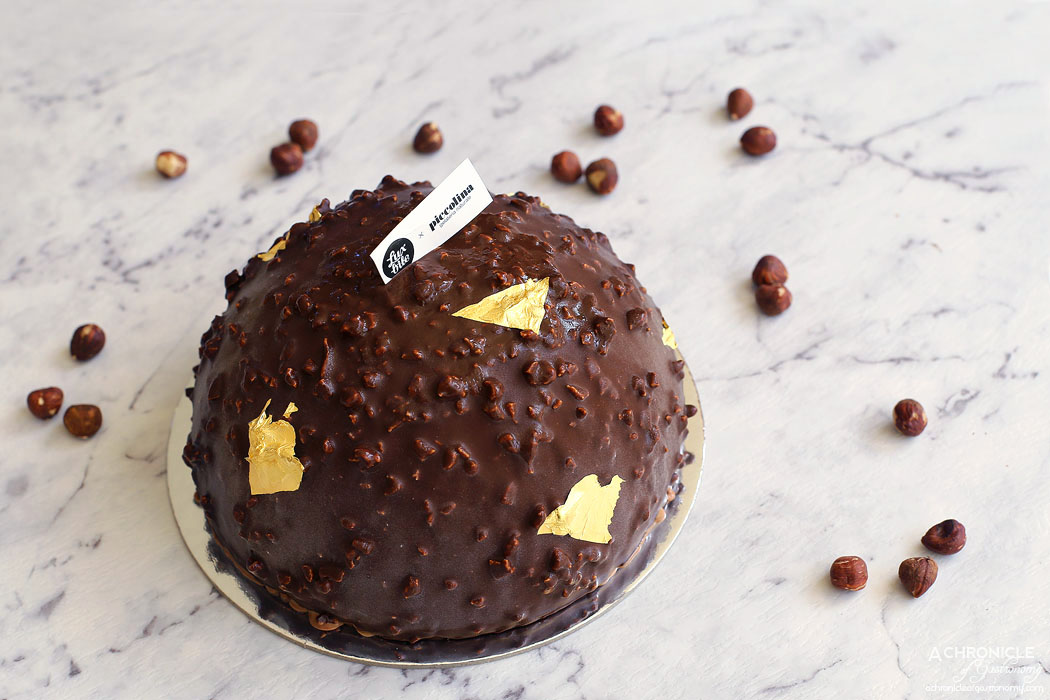 Piccolina Gelateria gelato cake - Ferrerolina Rocher - Hazelnut gelato, Better than Nut-ella gelato, hazelnut praline & puffed rice crunch, Milk Chocolate gelato, covered in dark chocolate with roasted hazelnut, gold flakes ($85)