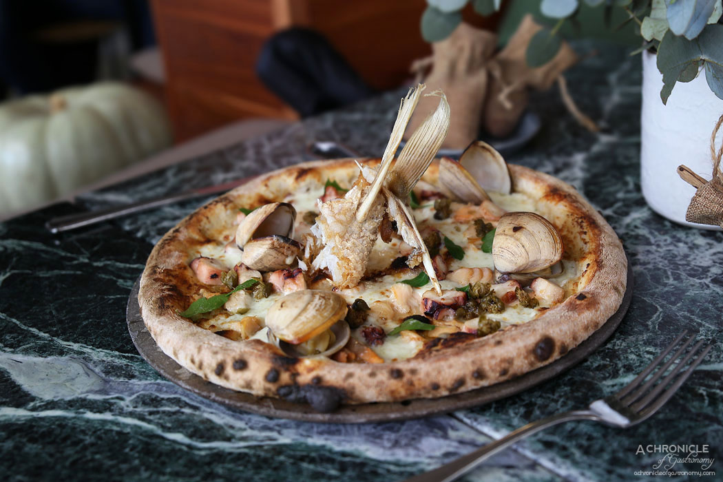Abacus - Seafood pizza - pickled octopus, clams, garlic, olive oil, buffalo mozzarella, smoked trout wings, sea parsley, capers ($25)