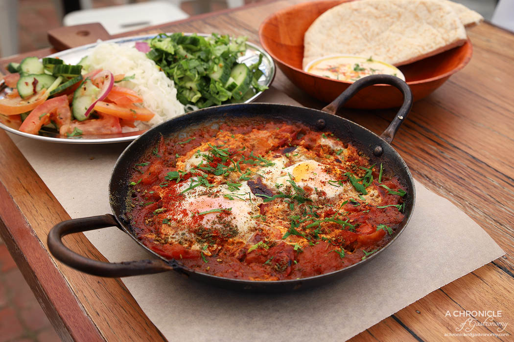 Tahina Fitzroy - Red Shakshuka - Two free range eggs with traditional tomato base with mixed herbs. Served with Israeli salad, spicy green salad, pickled cabbage, hummus, tahini and pita bread ($15.50)