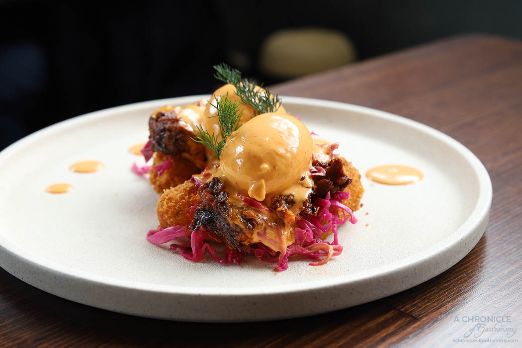 Cafe Louis - Benny - Pulled pork with pickled cabbage, poached eggs and sriracha bernaise on croquettes ($19.50)
