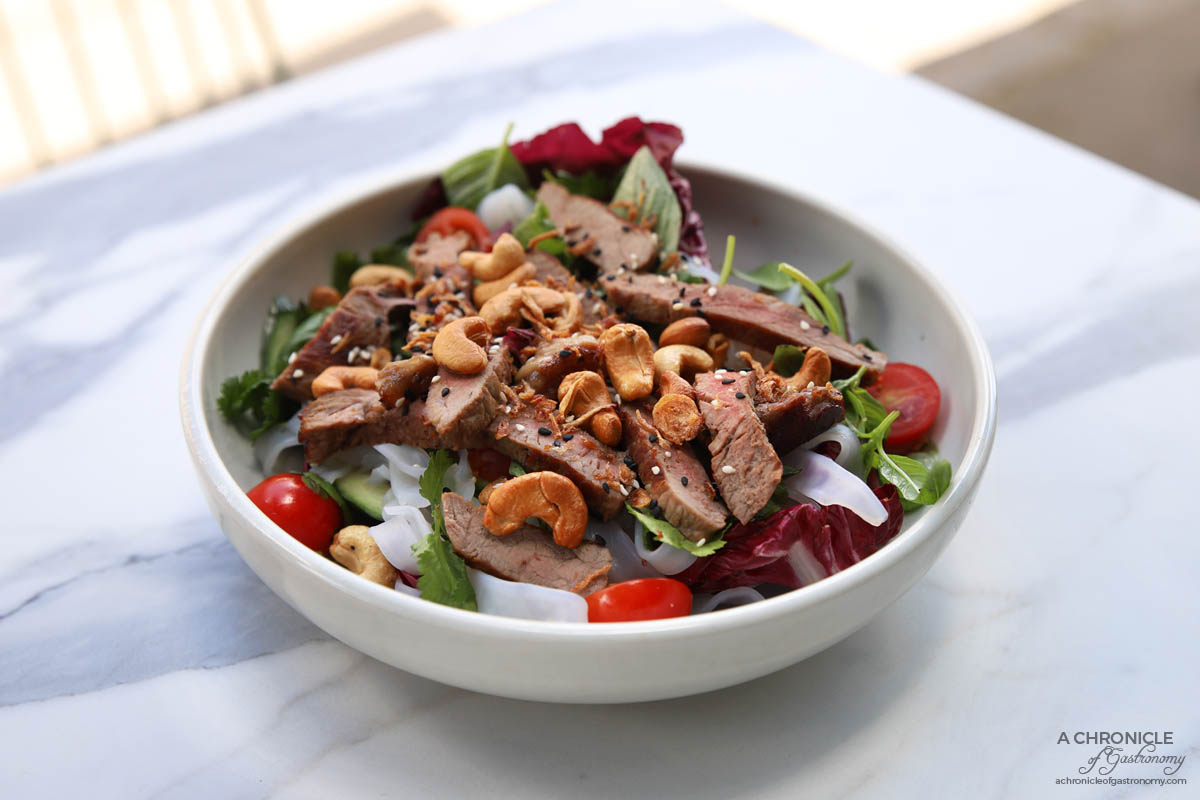 Riche - Crying Tiger, Hidden Dragon - Medium-rare sliced Porterhouse, coriander, mint, basil, cherry tomatoes, cucumber, radicchio, glass noodles, cashews, fried shallots, and nuoc cham dressing ($22)