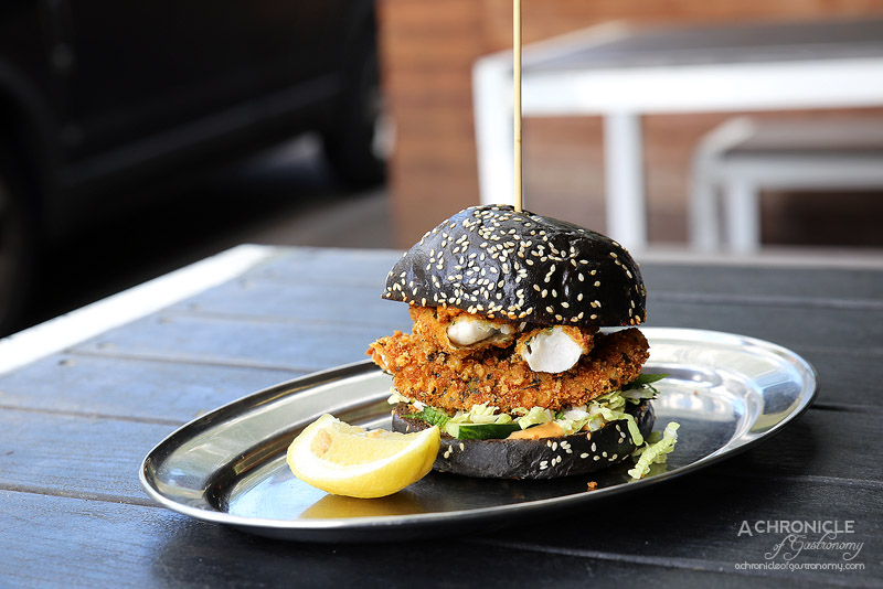 Tank Fish and Chips - Parmesan crumbed flathead fillet, mint and cucumber slaw, harissa mayo on a squid ink brioche bun