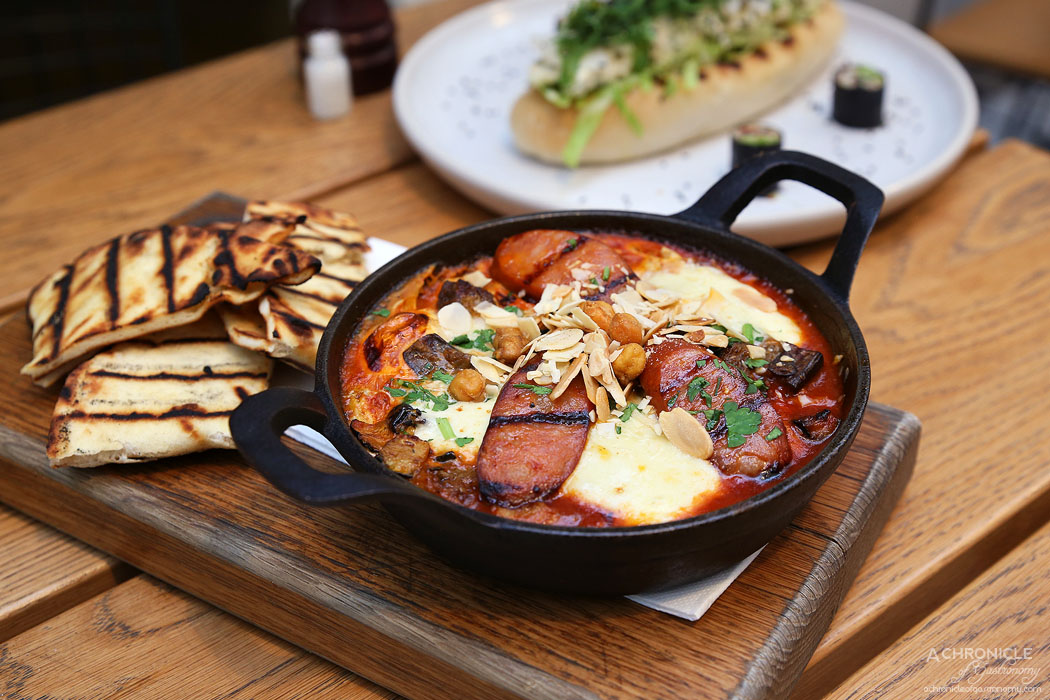 Mr Mister - Baked eggs shakshuka with chorizo crumb, spiced tomato and pepper sauce, mozzarella, grilled eggplant and zucchini, almonds, puffed chickpeas and grilled flatbread ($19)