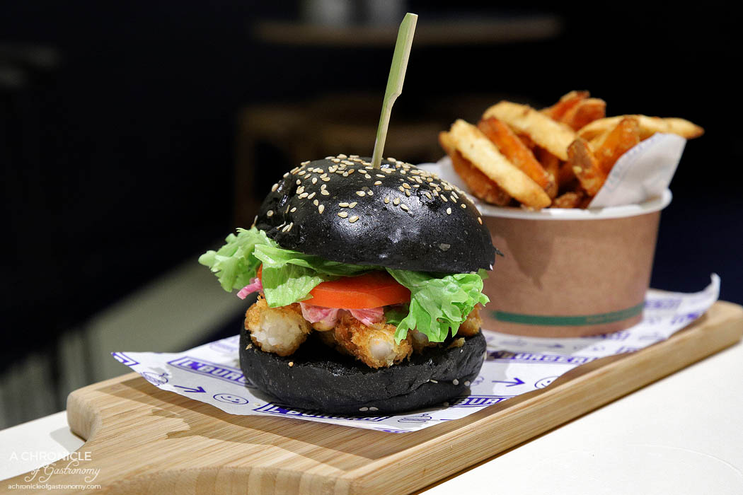 L'Burger - Prawn Noir - Toasted black Pain de Mie milk bun, lemon caper mayonnaise, salad mix, tomato, chipotle mayonnaise, and panko crumbed fried prawn cutlets ($15)